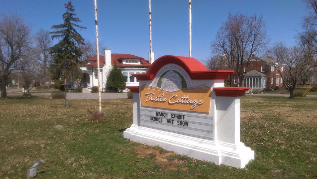 Muhlenberg County Public Libraries' Thistle Cottage logo sign.